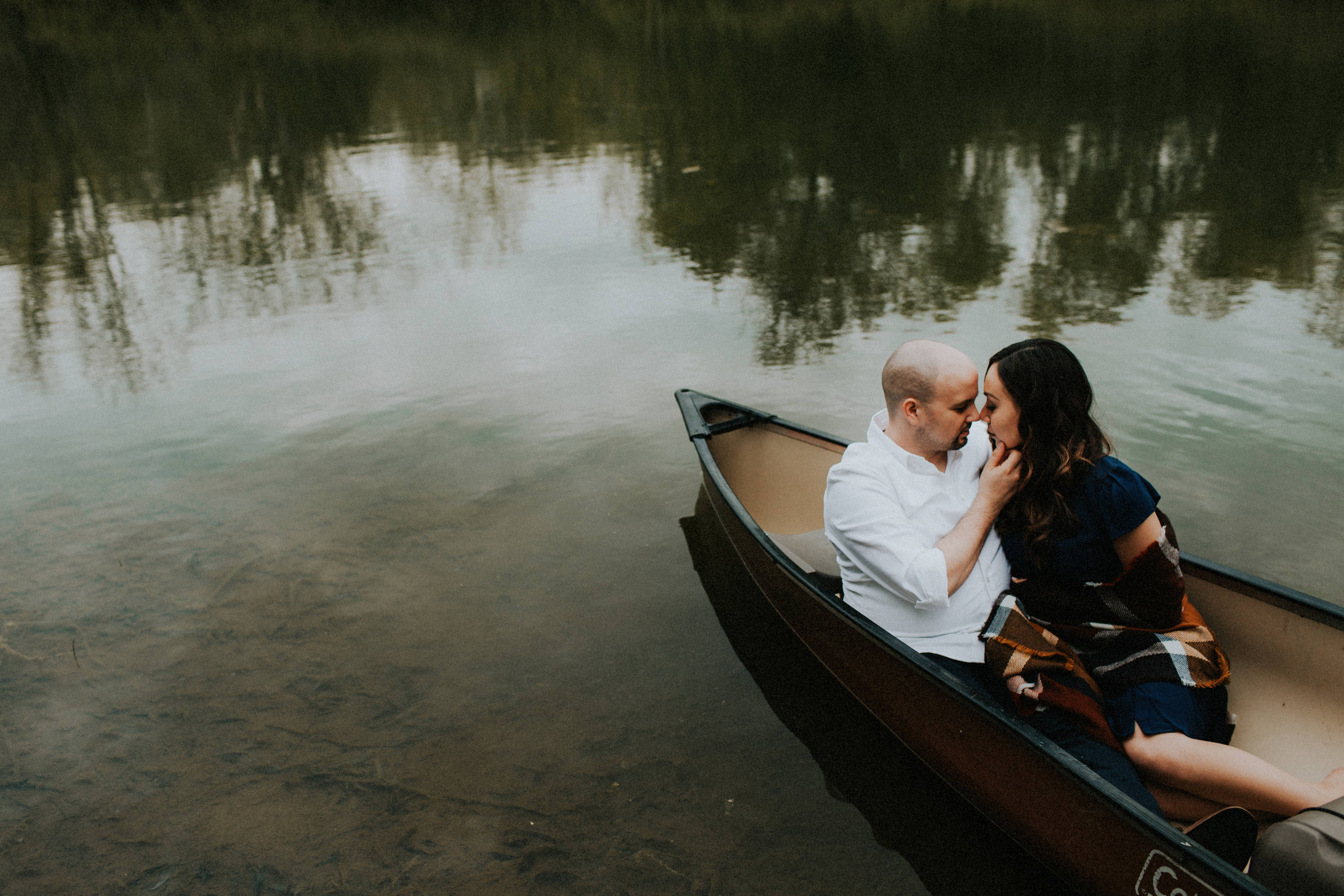bride and groom cuddled in canoe