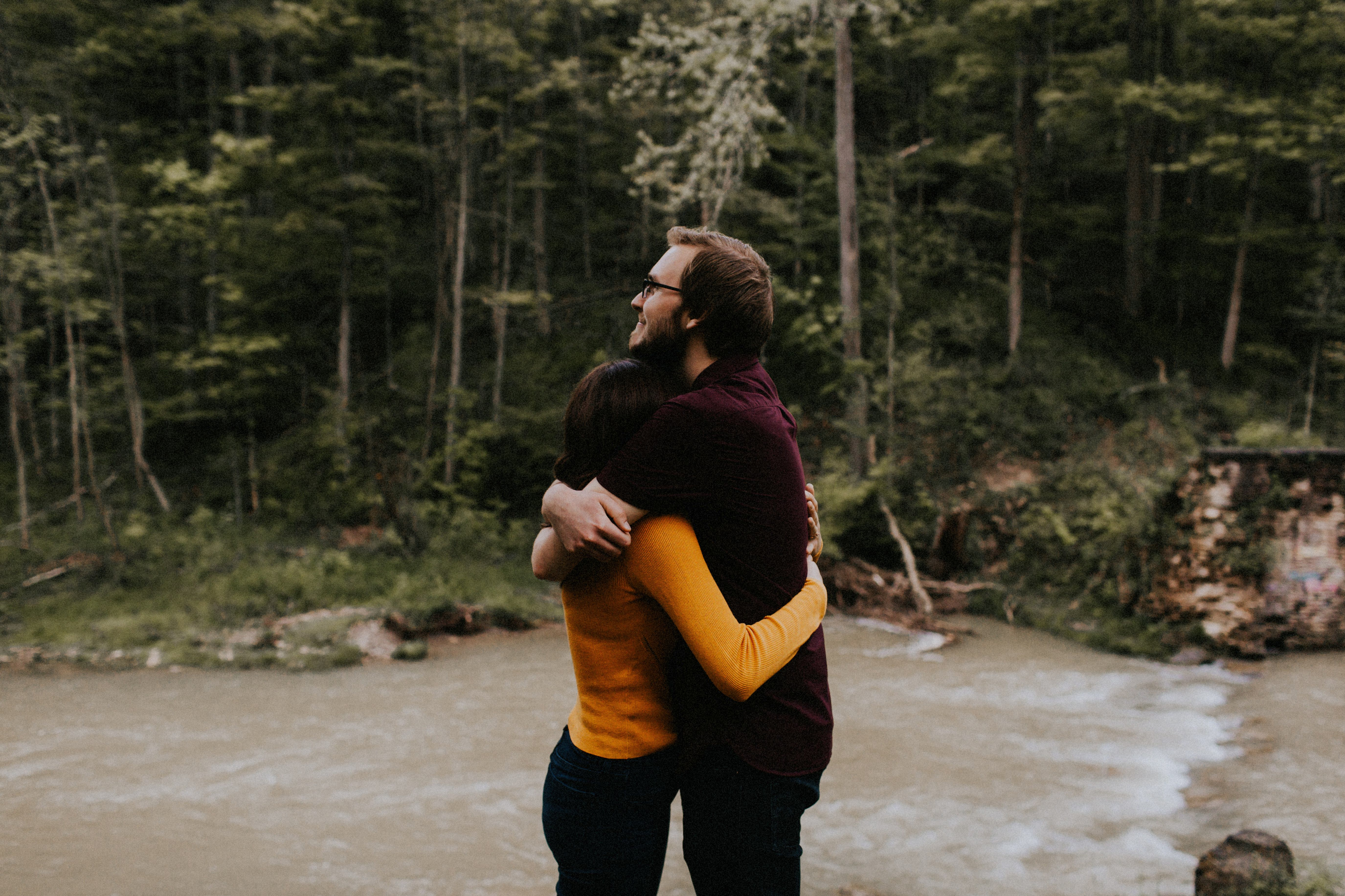 couple hugging by stream