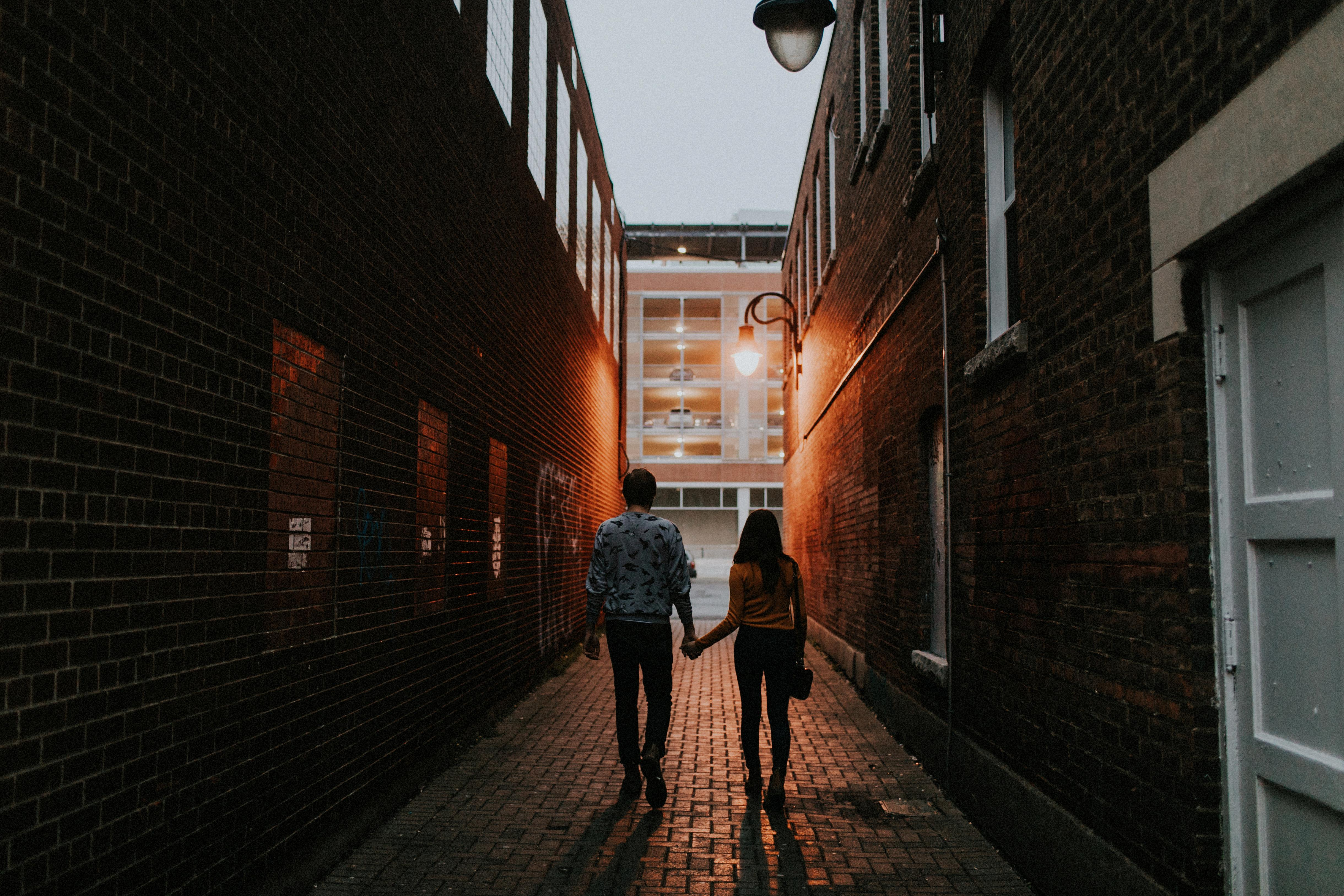 couple walking in alley way at night