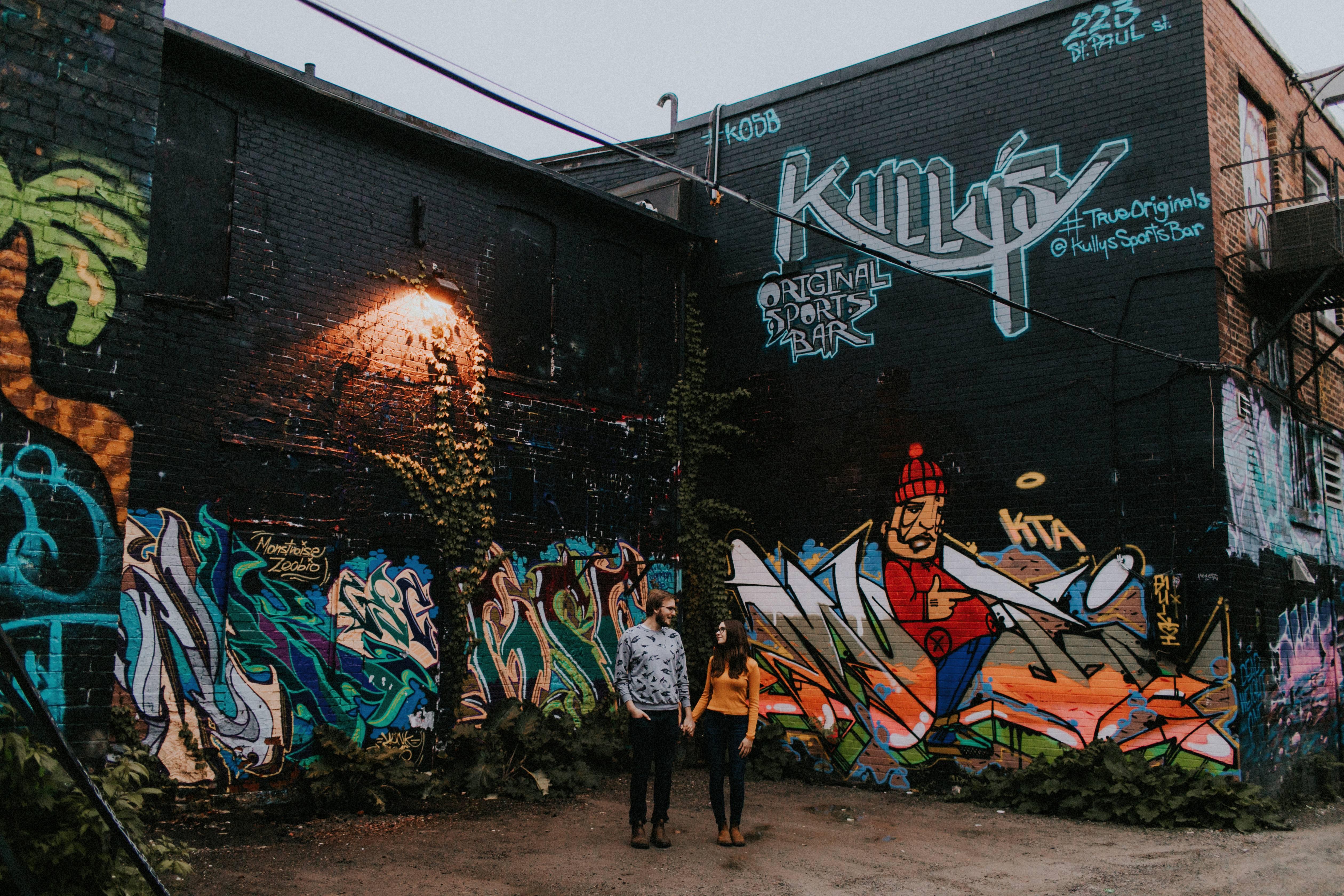 couple standing by graffiti