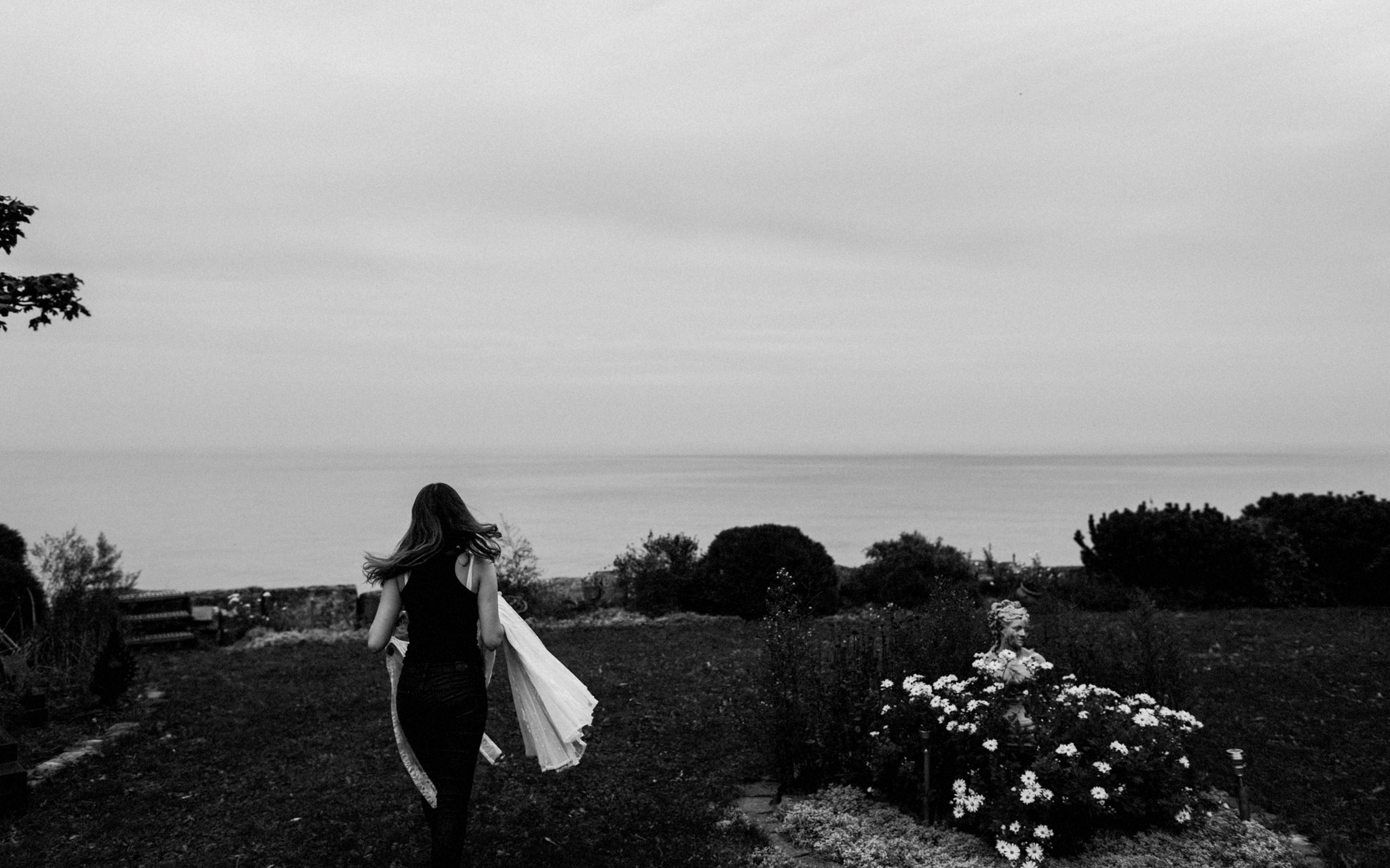 bride carries her wedding dress outside