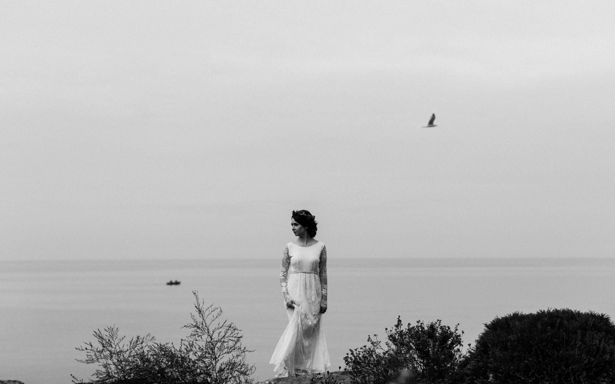 bride poses by water