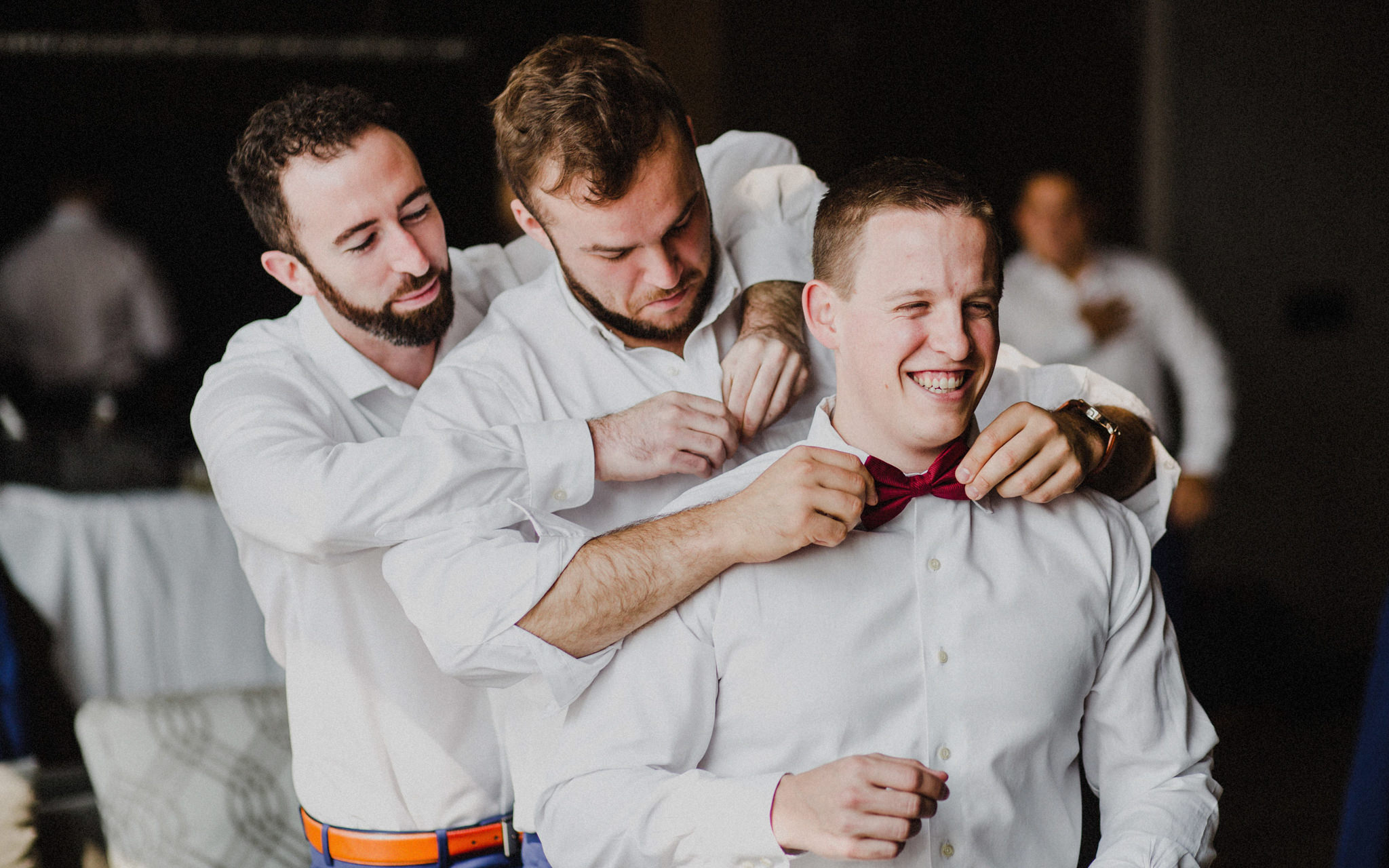 groomsmen help groom get ready