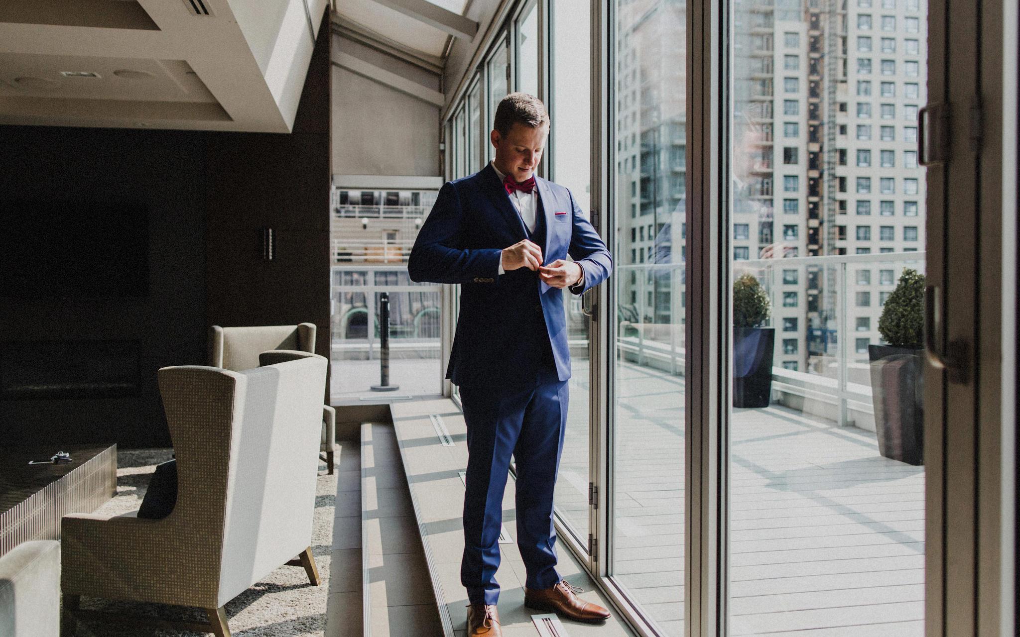 groom gets dressed by window