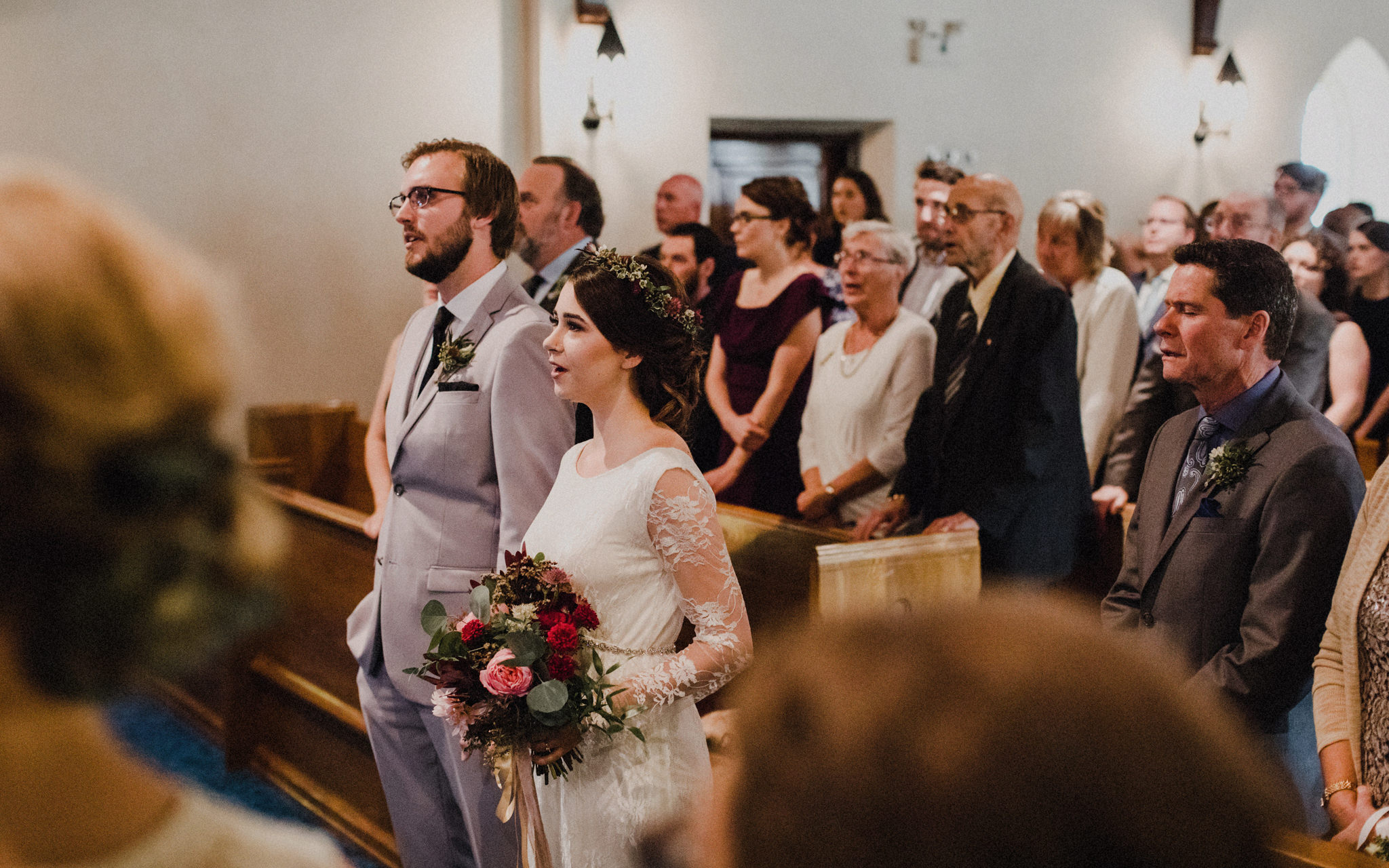 bride and groom sing in church