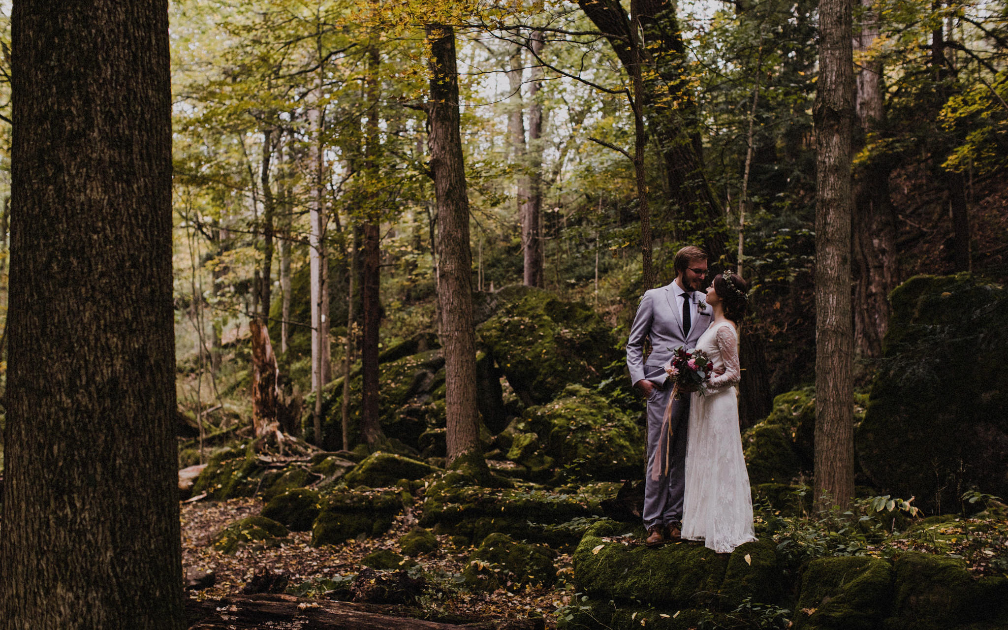 bride and groom stand on mossy rocks