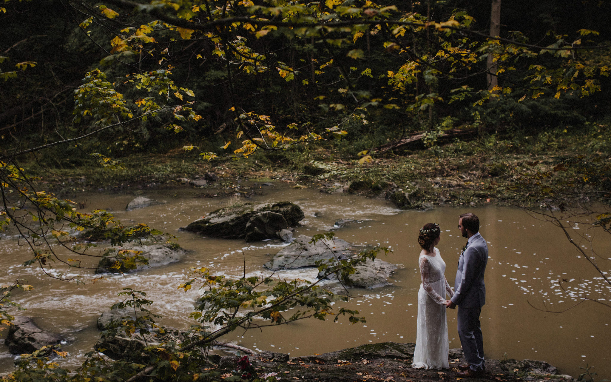 bride and groom stand by water