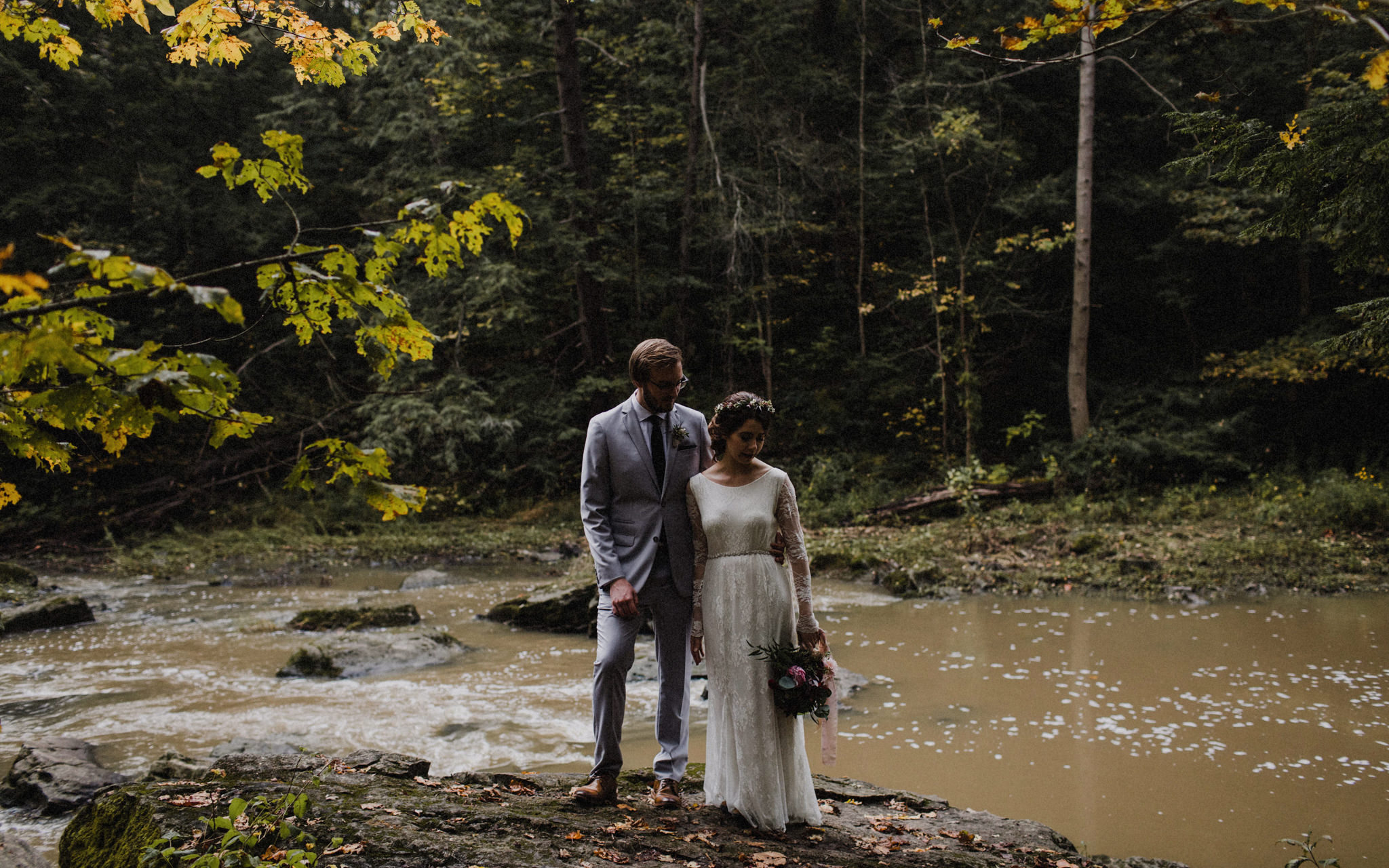bride and groom stand at water