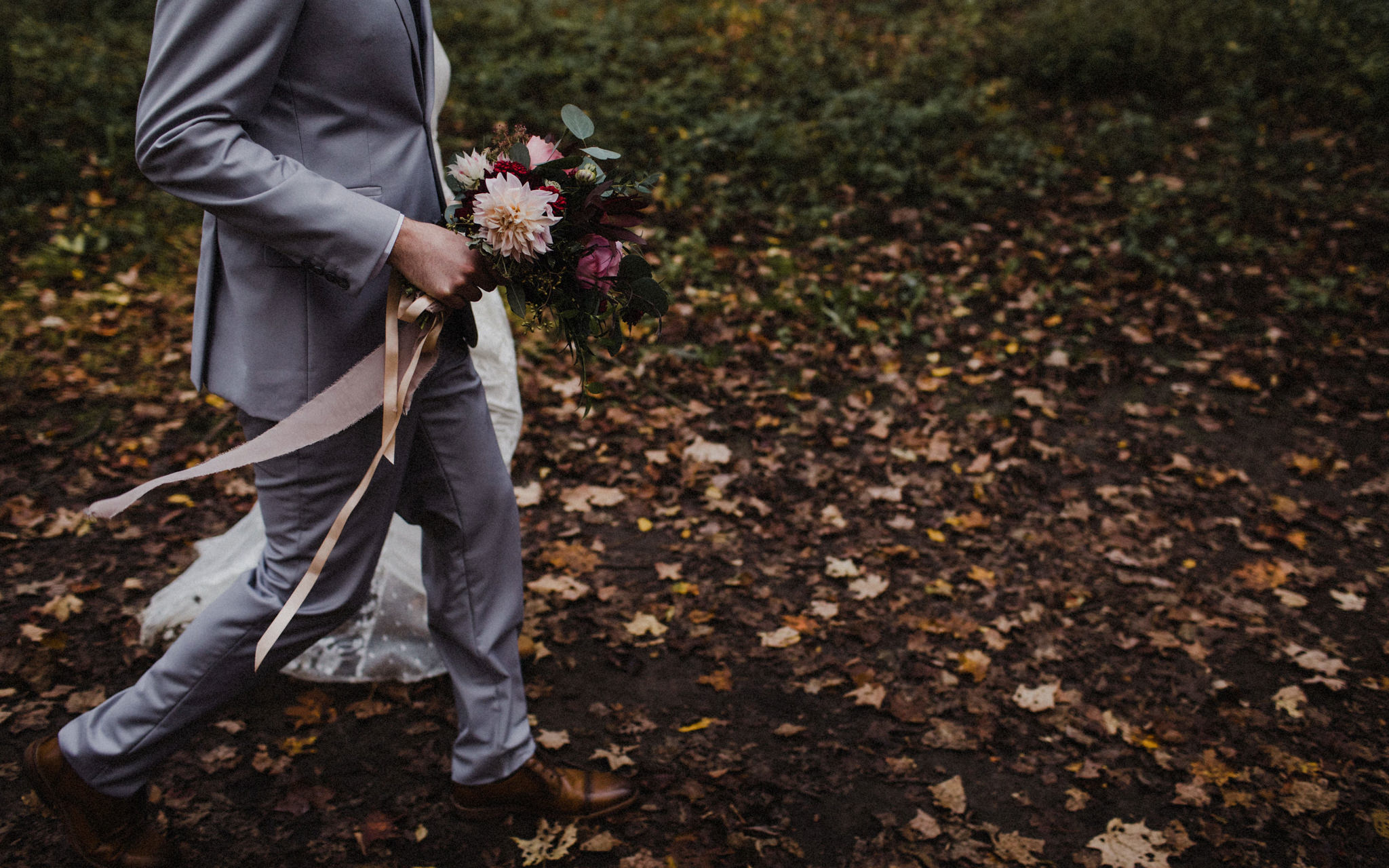 groom holds fall bouquet