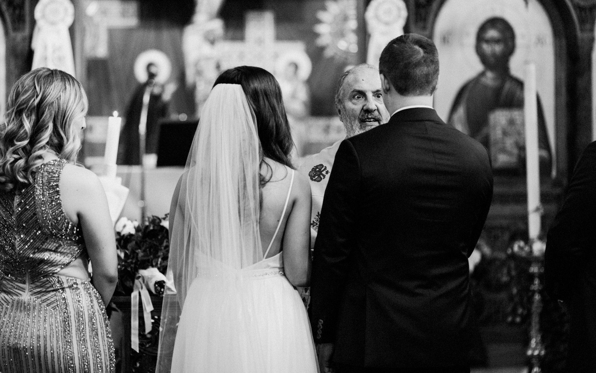 priest talks to bride and groom