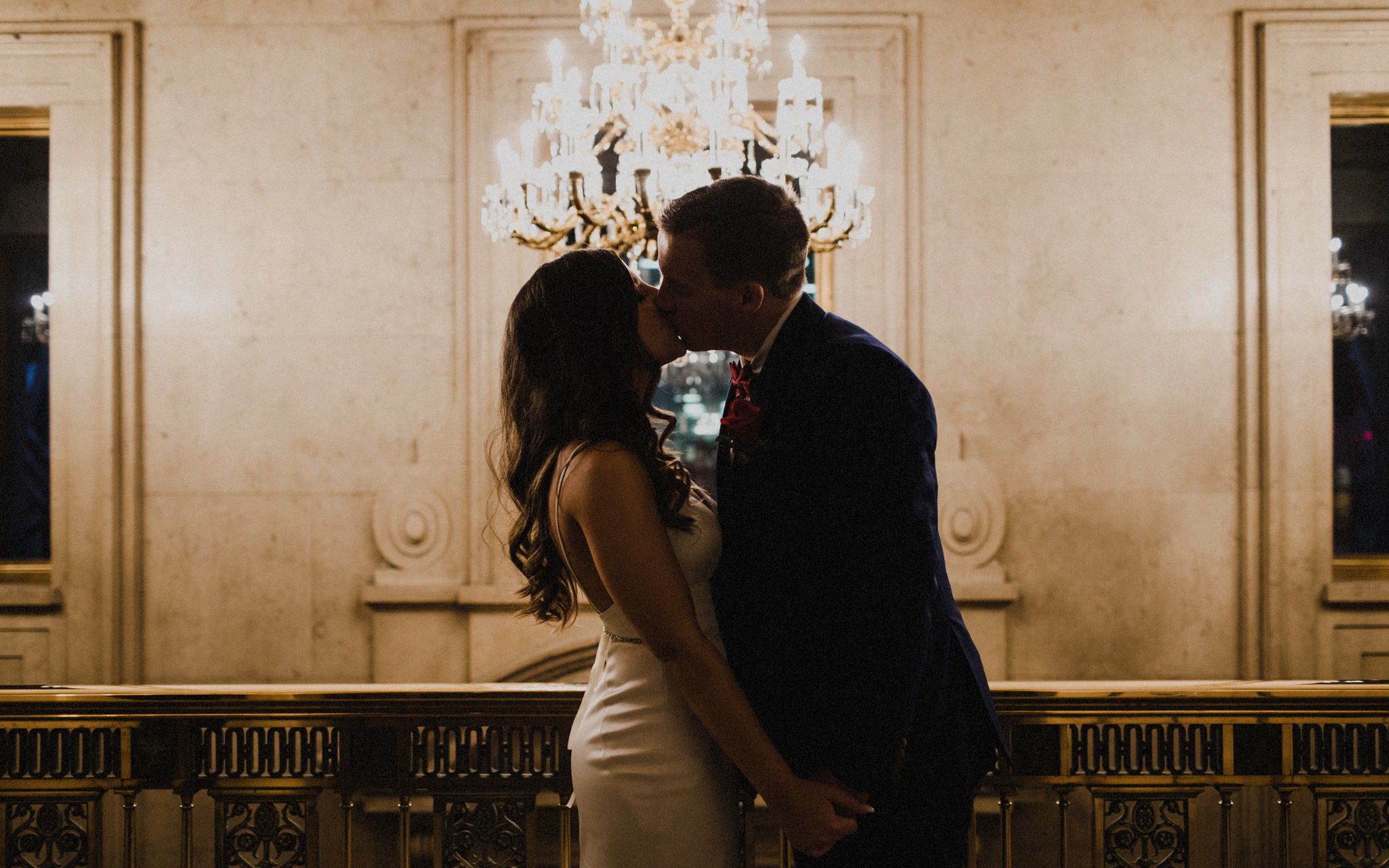 couple kissing by chandelier