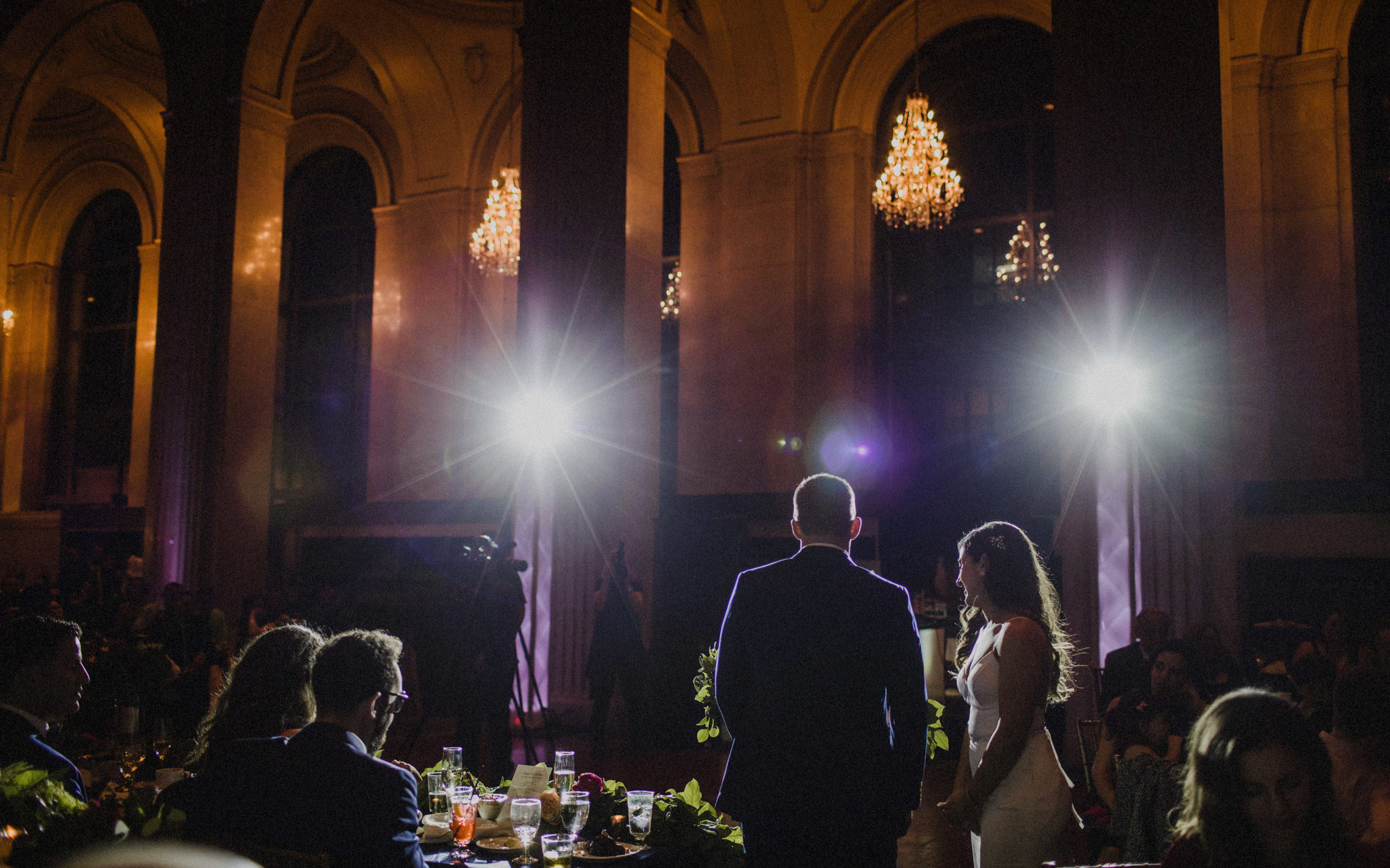 bride and groom give speech in spotlights