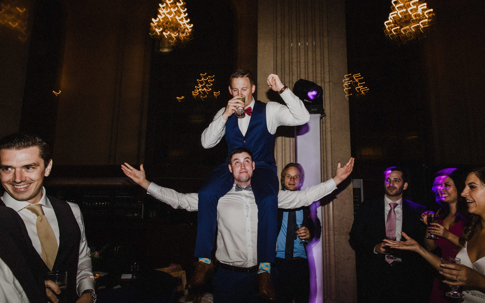 groom sits on shoulders of groomsman
