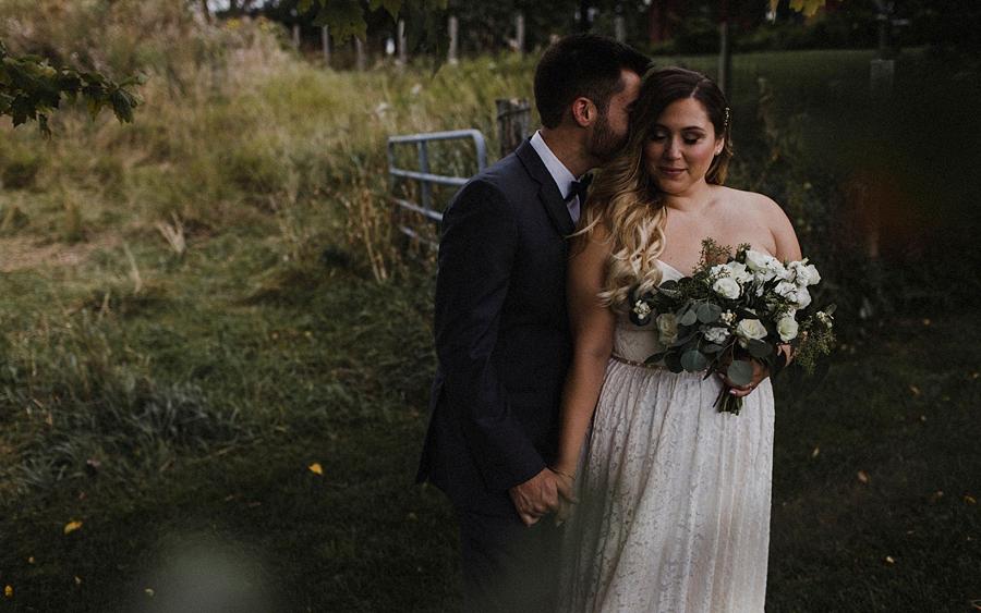 bride groom snuggle on farm