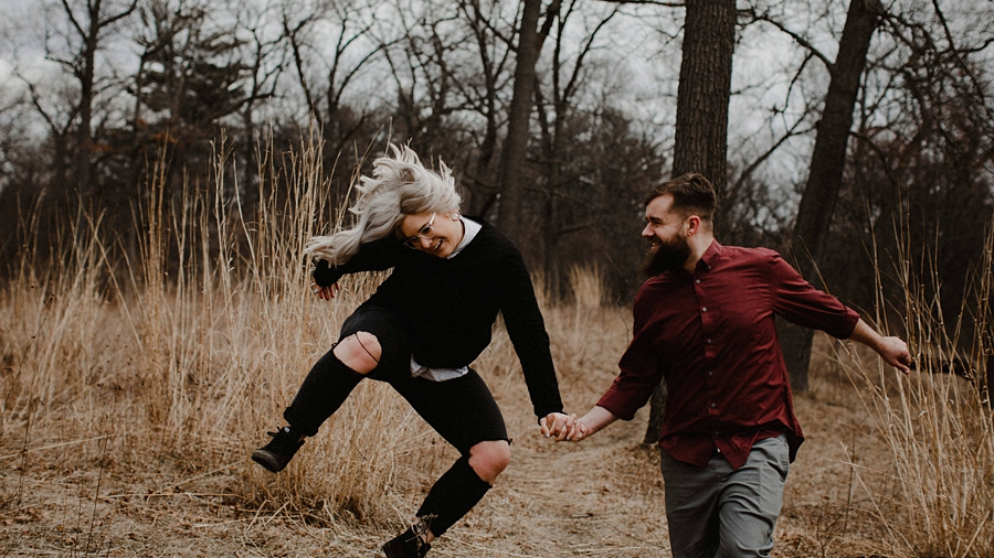 couple jumps in tall grass