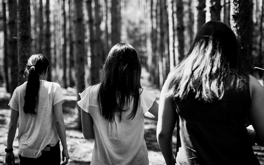 three girls walking into forest