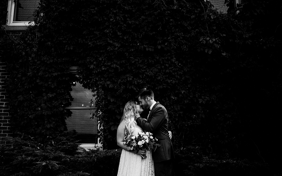 bride groom kiss by ivy wall