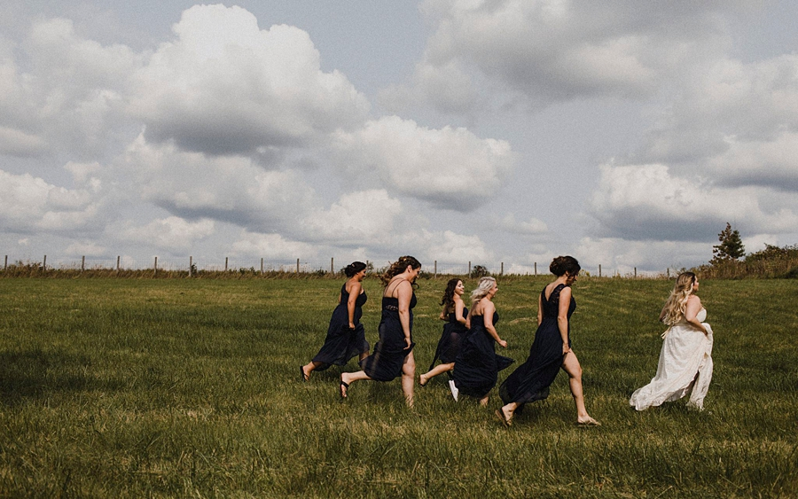 bridesmaids run through wheat fields