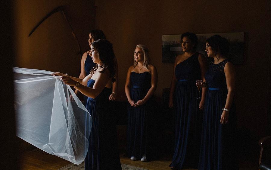 bridesmaids help put veil on