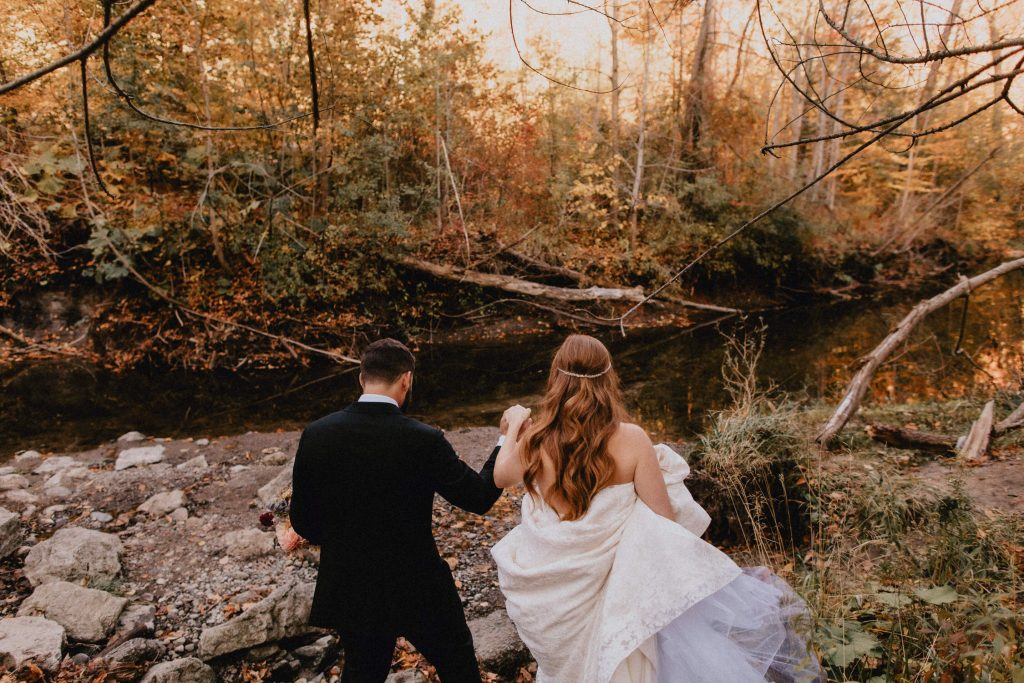 Bride and groom walk through forest towards river - Autumn Micro Wedding at Berkeley Fieldhouse