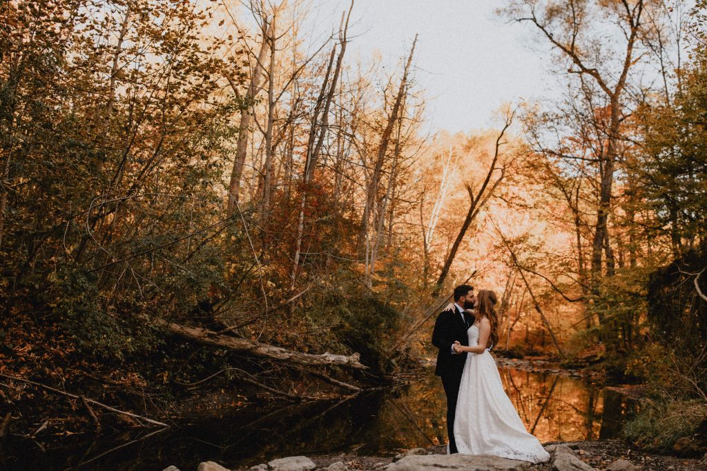Bride and groom kiss beside river in back-lit forest - Autumn Micro Wedding at Berkeley Fieldhouse