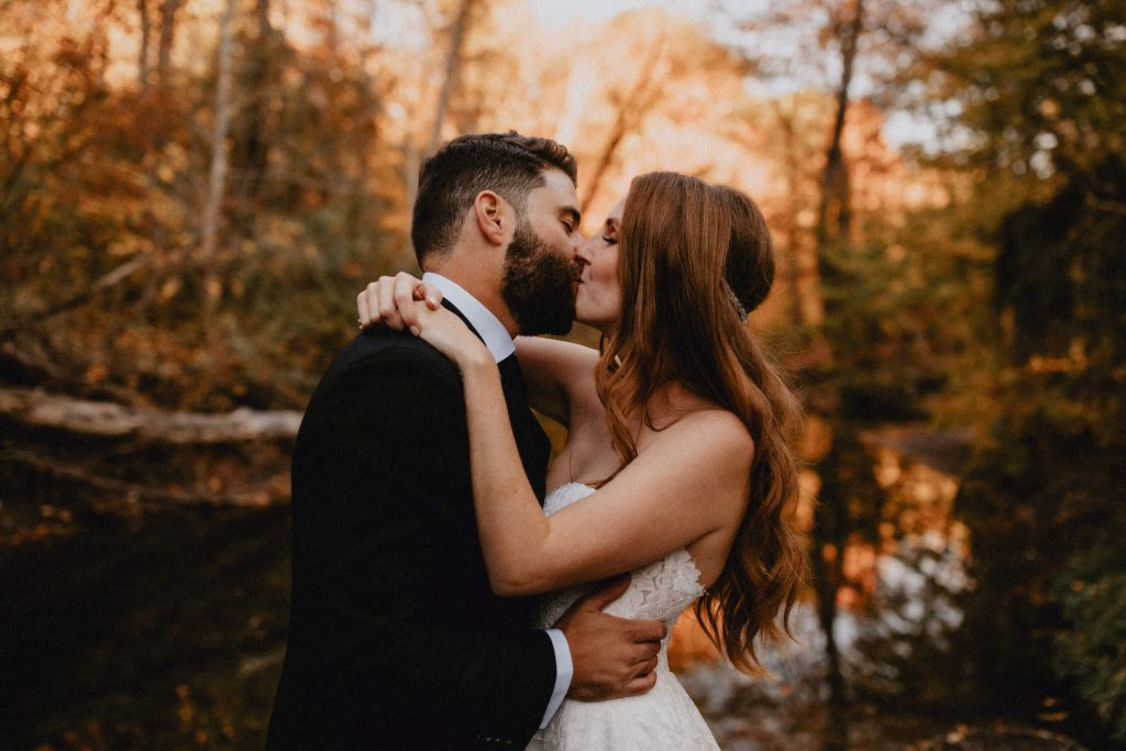 Bride and groom kiss by the river - Autumn Micro Wedding at Berkeley Fieldhouse
