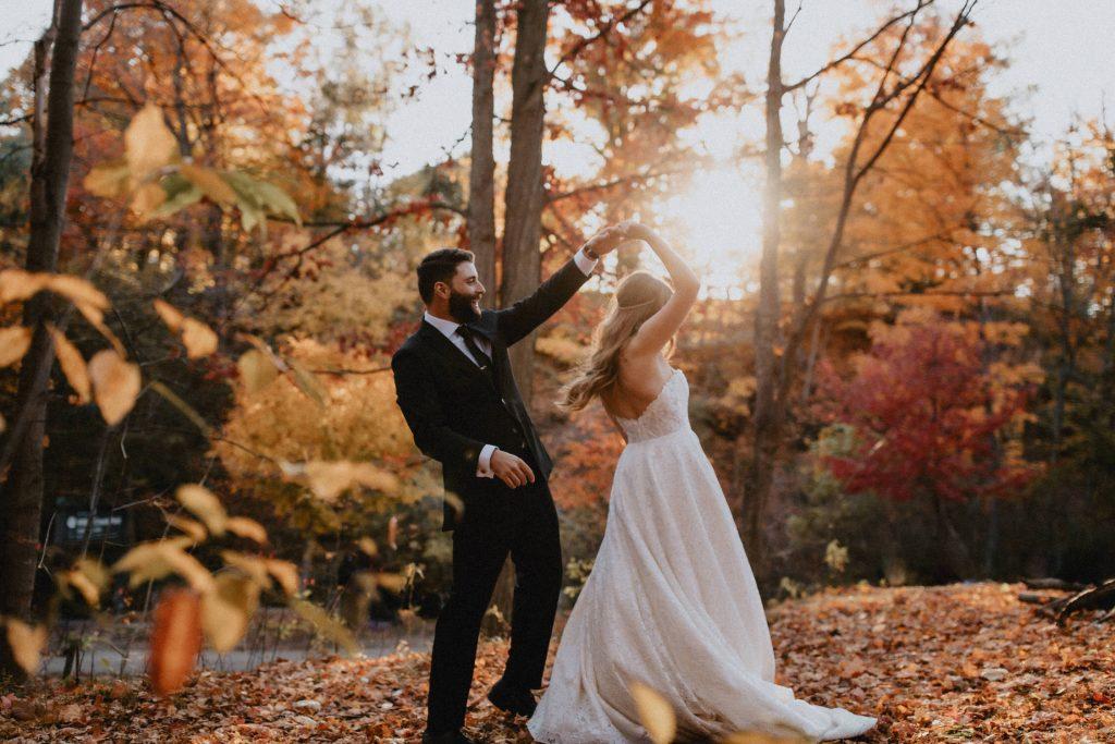 Groom Twirls bride through the fall leaves - Autumn Micro Wedding at Berkeley Fieldhouse