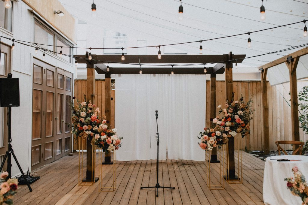 Wooden Alter with warm toned floral arrangements and string lights - Autumn Micro Wedding at Berkeley Fieldhouse