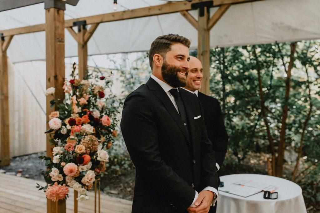 Groom smiles as bride walks down the aisle - Autumn Micro Wedding at Berkeley Fieldhouse