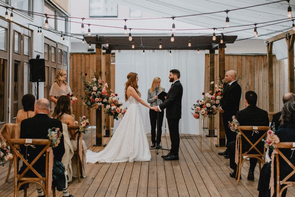 Bride and groom holding hands at the alter - Autumn Micro Wedding at Berkeley Fieldhouse