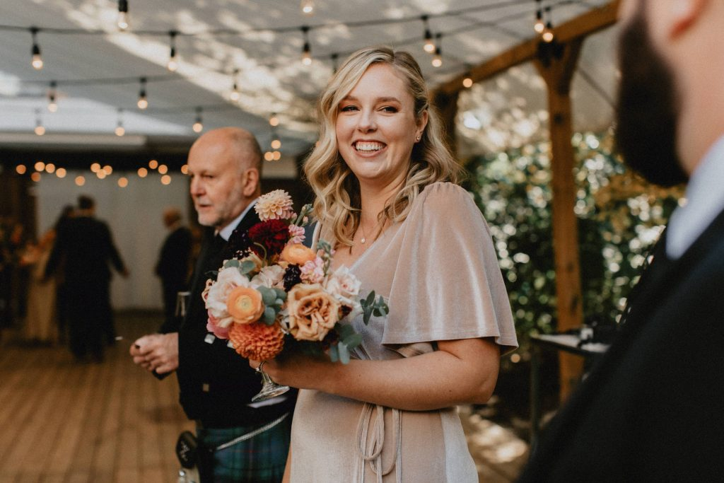 Bridesmaid smiles with bouquet - Autumn Micro Wedding at Berkeley Fieldhouse