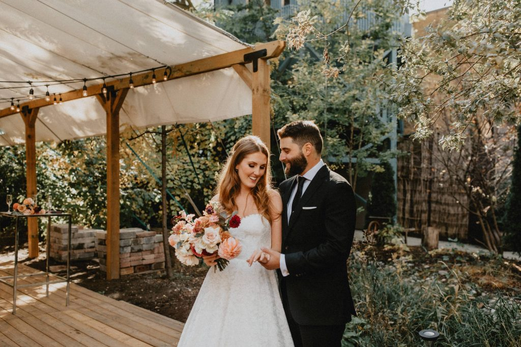 Bride and groom embrace while holding hands - Autumn Micro Wedding at Berkeley Fieldhouse