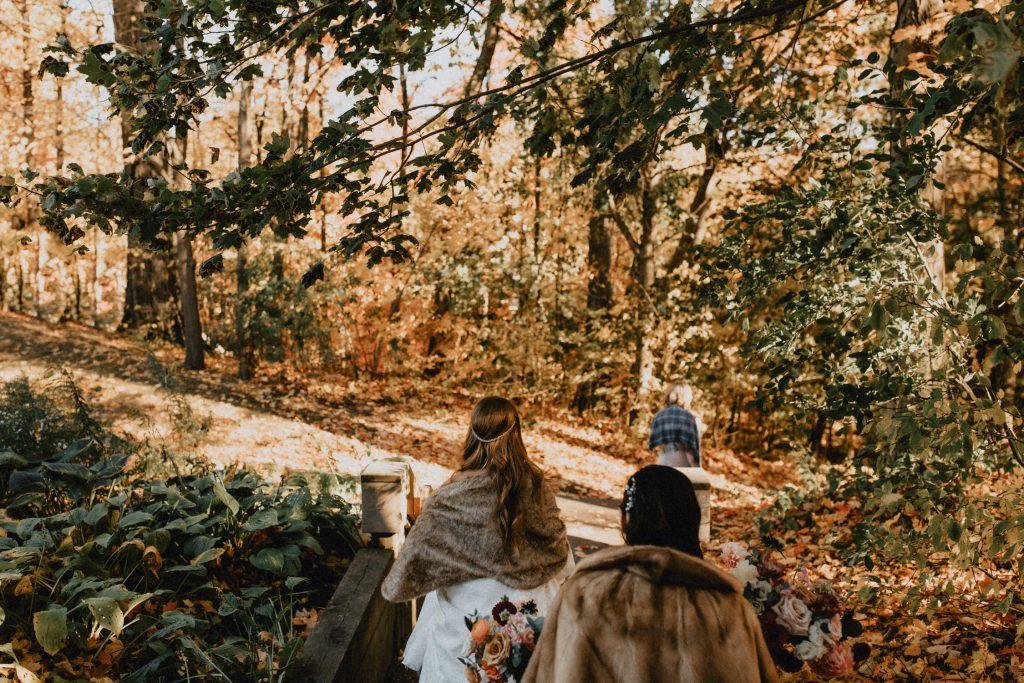 Wedding party walks through sunlit forest - Autumn Micro Wedding at Berkeley Fieldhouse
