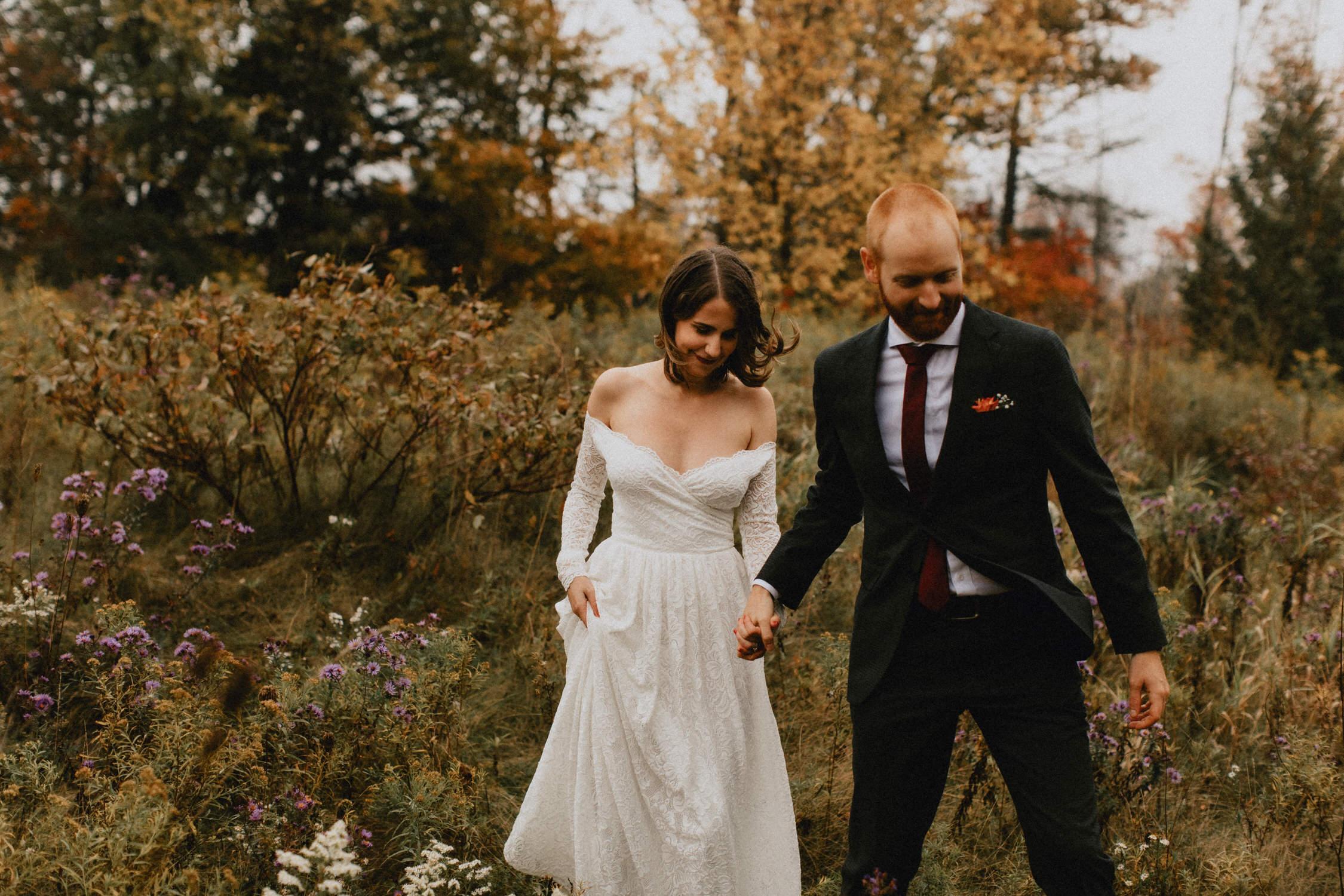 Groom leads bride through wildflower field - Huron Natural Area Micro Wedding Kitchener, Ontario