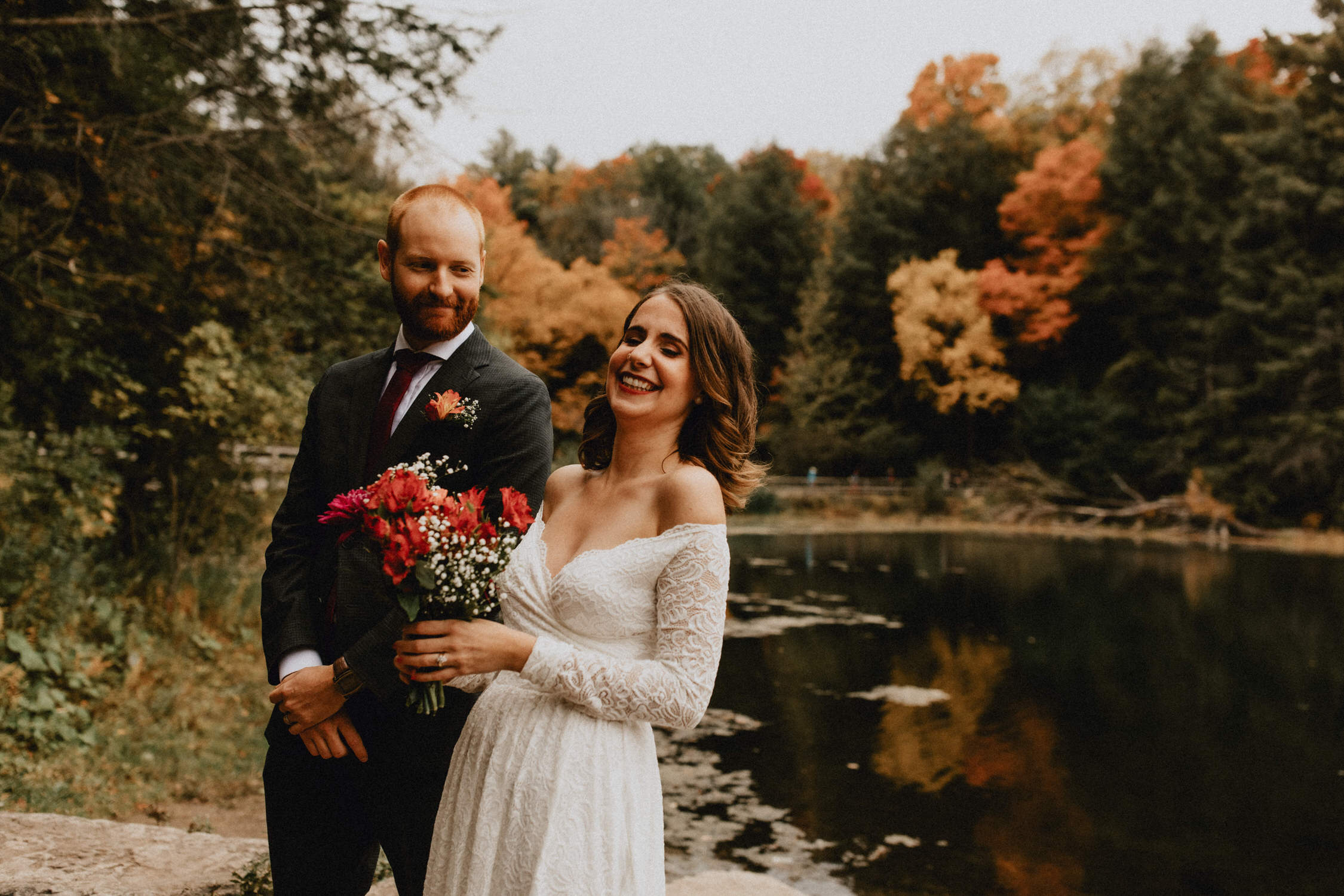 Bride laughs during fall wedding ceremony near pond - Huron Natural Area Micro Wedding Kitchener, Ontario