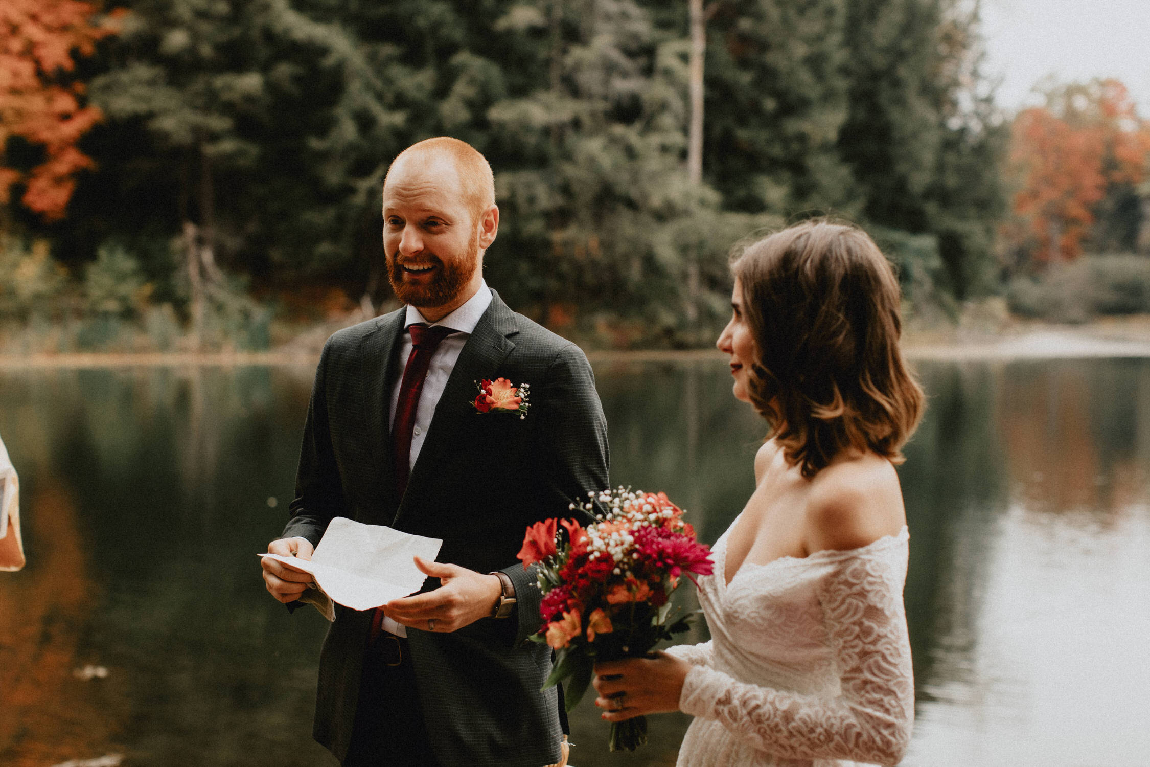 Groom smiles reading vows in the forest - Huron Natural Area Micro Wedding Kitchener, Ontario