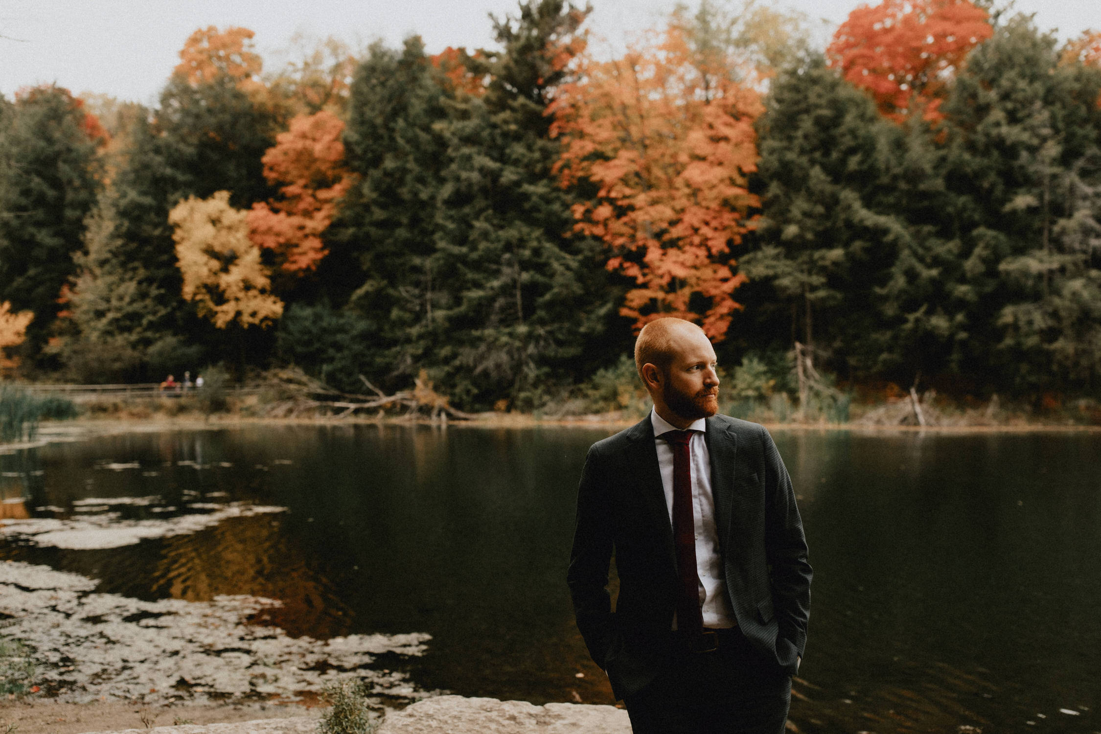 Groom near pond and fall trees - Huron Natural Area Micro Wedding Kitchener, Ontario