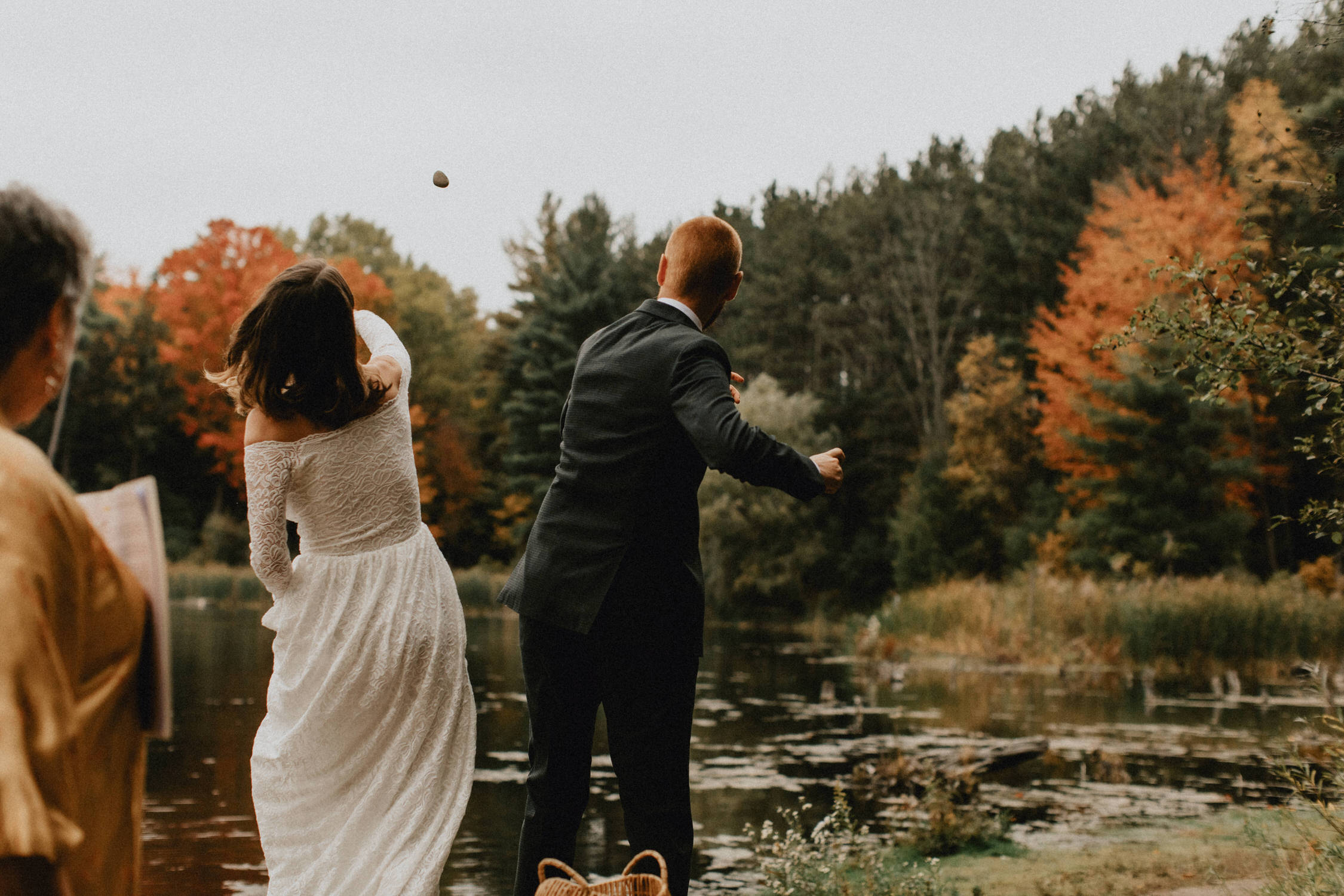 Bride and groom throw rocks in the pond to make a wish - Huron Natural Area Micro Wedding Kitchener, Ontario