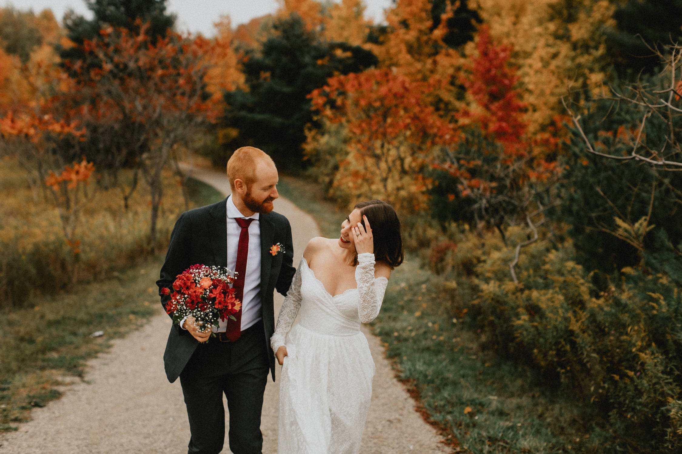 Bride and groom walk through park in fall - Huron Natural Area Micro Wedding Kitchener, Ontario